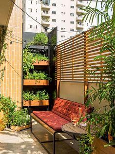 No terraço desse apartamento com cara de casa, uma horta vertical e painel com madeira ripada.