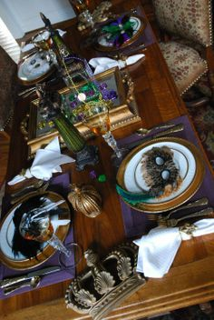 Mardi Gras-inspired table with fleur-de-lis napkin rings, gold flatware, requisite crowns, doubloons, beads, and masks at each place setting. #MardiGras