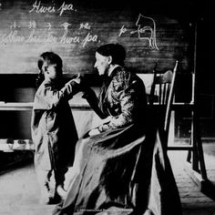 This lady is teaching a deaf child at a private missionary school in 1900 with hair in a tight bun.