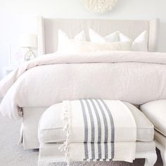 Monochromatic bedroom features a linen slipcovered wingback bed dressed in linen bedding alongside a pair of french linen stools.