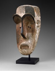 Mask (bikeghe) Late C 19 - early C 20 - Masks such as this one appeared in Fang initiations and at other ceremonial occasions largely concerned with community crisis and protection. Some of these masks are elongated, others have two or four faces. Both types frequently show white, heart-shaped faces framed by arching brows. This large mask with variegated coloring is called bikeghe and is said to represent a part-human, part-animal force responsible for ensuring soci