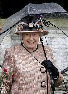 Britain's Queen Elizabeth II laughs as she shelters under an umbrella after attending the annual Christmas day morning service at Sandringham Church