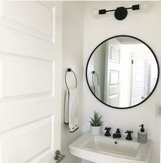 Black modern two light wall sconce in a black and white bathroom that has a black mirror and a white pedestal sink. Bathroom Wall Colors, Small Bathroom Mirrors, Bathroom Mirror Lights, Small Bathtub, Bathroom Sconces, Mirror With Lights, Bathroom Interior, White Bathroom, Black Bathroom Light