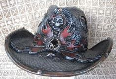 Playa cowboy hat with skulls - A perennial favorite of Burners. Flames and teardrop shaped vents, black glass stones. This one is in dark pewter and red with a few skulls, roses and star accents. It will keep the sun off in style. $175.00