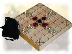 Brandub, a version of the Viking game hnefatafl that was played in Ireland.  One player must help the king escape to one of the four corners, while the other player must capture the king before this happens.