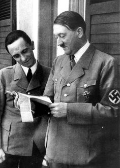 Hitler appears amused from reading a newspaper clipping offered by propaganda chief Goebbels, who's smiling his approval. Hitler was an avid reader of the press. His daily routine usually opened with a thorough reading of press briefings prepared by his press secretariat run by Otto Dietrich, his press chief, who was not on good terms with Goebbels.