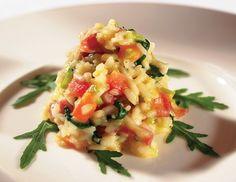 Für das Rucolarisotto mit Parmaschinken den Knoblauch feinwürfelig, den Lauch in feine Streifen schneiden und die gewaschene Rucola grob hacken.
