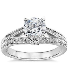 Beautifully crafted, this platinum engagement ring features two French pavé-set bands that form a reverse split shank (a band that splits on the sides of the ring rather than at the front like a traditional split shank).