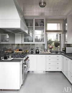 The kitchen has a Wolf range, E. R. Butler & Co. cabinet hardware, a silver-leafed ceiling, and a floor of French Blue limestone by Ann Sacks.