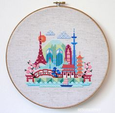 This cross stitch pattern of a stylized Tokyo skyline features the Tokyo Tower, the Rainbow Bridge, the Tokyo City Hall, the Mode Gakuen Cocoon