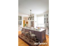 """The new kitchen on the main floor was built on top of original floors. The lavender, quartz-topped island and the glass-front cupboards are filled with vintage serving dishes. The old highchairs serve as stools around the island.    See more of this home in """"Colourful Heritage Victorian Anything but Gloomy"""" from OUR HOMES Barrie Spring 2017:  http://www.ourhomes.ca/articles/build/article/colourful-heritage-victorian-anything-but-gloomy"""