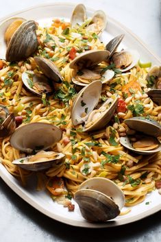 NYT Cooking: Briny clams come together with smoky bacon and sautéed leeks in this showstopper. Quick to prepare, this weeknight recipe is decidedly sophisticated. First, sauté the bacon, add the garlic and leeks and add some good white wine and tomatoes. Toss with al dente linguine and top with clams and lemon juice. Finish with it with parsley and pine nuts, and pour yourself a gl...