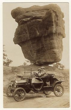 "1920s Young couple driving past ""Balanced Rock"" in the Garden of the Gods, Colorado Springs, Colorado."