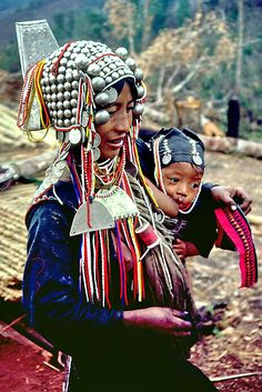 An Akha mother wears a traditional silver headdress as she breastfeeds her young baby and appliques cloth that she will stitch into clothing. At night, she wears her heavy headdress, beads and jewelry to bed. Her babies cap is also decorated with silver coins and glass beads. The Akha, one of the most exquisitely dressed peoples in Asia, are one of several tribes that live in the mountains of China, Thailand, Laos and Burma | © John Spies