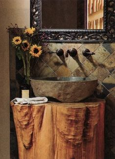 Awesome bathroom vanity made from a huge tree stump with a beautiful rustic basin and beautiful faucet and mirror. Love it!