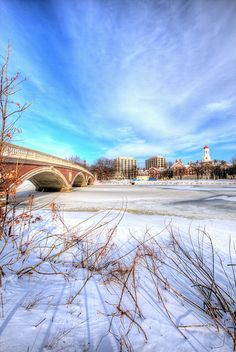 View of the Weeks Footbridge over the frozen Charles River, with Harvard University on distant shore.