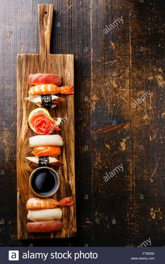 Download this stock image: Nigiri Sushi set on serving board on wooden background - FT8D0D from Alamy's library of millions of high resolution stock photos, illustrations and vectors.