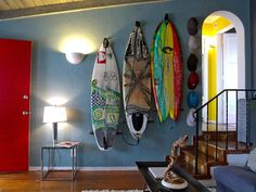 - Colorful Coastal Design on HGTV - Kevin Mincin's California home mixes bold colors like a sunny yellow room and a red door with slate blue walls. A collection of colorful surfboards on the wall serves double duty as display and storage. Home Design, Interior Design, Coastal Homes, Coastal Living, Coastal Farmhouse, Bohemian Living, Coastal Cottage, Coastal Style, Coastal Decor