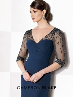 Chiffon slim A-line gown with hand-beaded illusion three-quarter sleeves and V-neckline, surplus pleated sweetheart bodice, beaded illusion keyhole back, inset sweep train. Sizes: 4 – 20, 16W – 26W Color: Navy Blue