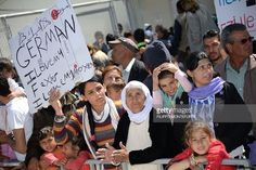 Migrants and refugees hold placards reading messages at the Moria refugee camp on April 16, 2016 near the port of Mytilene, on the Greek island of Lesbos. Pope Francis received an emotional welcome today on the Greek island of Lesbos during a visit aimed at showing solidarity with migrants fleeing war and poverty. Pope Francis, Orthodox Patriarch Bartholomew and Archbishop Jerome visit Lesbos today to turn the spotlight on Europe's controversial deal with Turkey to end an unprecedented…