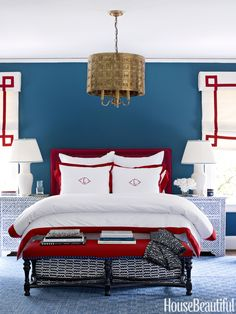 This large guest room in Charlotte, North Carolina needed graphic punch. Designer Lindsey Coral Harper painted the walls Benjamin Moore's Van Deusen Blue, which allows the red bed and window accents to stand out.   - HouseBeautiful.com