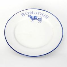 Part of our farmhouse dining collection, the white Bonjour salad plate comes trimmed in blue with a decorative cow stamp under the lightly distressed script.