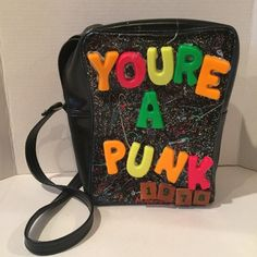 Handmade by me (Maxeene Davlin) 'You're A Punk 1978' bag. Strap is adjustable. Fridge magnet style letter and wooden block numbers on a hand splatter painted glitter acrylic. Zip closure on top. Bag is a vintage leather style cassette recorder carry case. This is the first of my bag designs and is completely One Of A Kind!! If you'd like more photos, let me know! Tags: nasty gal dolls kill unif punks x block letter purse messenger bag leather vintage up cycled unique hand made minus light