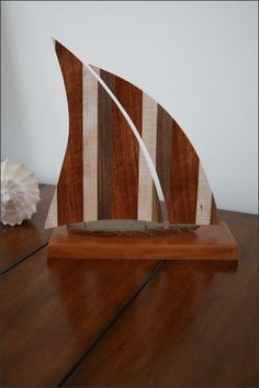 Handcrafted Wood Sailboat - This sailboat is handcrafted with five different hardwoods. The base is Cherry, the hull is Brown Heart, and the sails are Brazilian Cherry, Maple, and Walnut hardwoods laminated together.  This makes a great gift for many occasions including Birthdays, 5 Year Anniversary, or for yourself. Sailboat Lovers, Sailboat Collectors, or Nautical Lovers of all ages will love it.