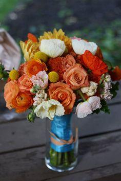Wedding bouquet made using orange unique roses, billy balls, poppies, dahlias, ranunculus, peach stock