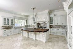 Traditional kitchen with white cabinets, honed travertine floors and wood counter island with large chandelier