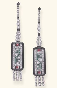 AN ELEGANT PAIR OF ART DECO MULTI-GEM AND ENAMEL EAR PENDANTS. Each rectangular pavé-set diamond plaque, enhanced by calibré-cut emerald and ruby detail, with black enamel trim and a single-cut diamond fringe, suspended by a similarly-set diamond and onyx line, mounted in platinum and 18k gold, circa 1925, with French assay marks. #ArtDeco #earrings