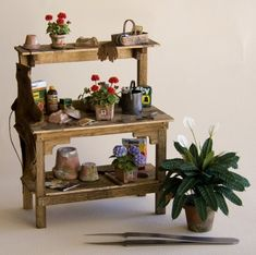 1/12th scale fully accessorized potting bench with handcrafted geraniums and hydrangeas, plus a potted spathiphyllum, by Bev Gallerani.  See the tweezers for scale.