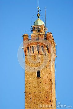 Photo made at the Asinelli tower in Bologna in Emilia Romagna (Italy). The picture shows the base of the tip, a square section with four merlons per side. The tip is formed by a small dome with a over a sphere and a cross. Is the background to the tower lit by the sun on blue sky.