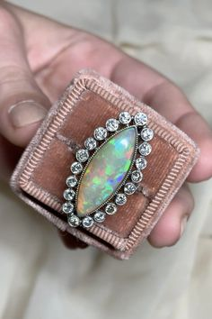 Vintage ring set with a navette cabochon opal measuring approximately 23.0 x 7.3 x 4.2 mm, surrounded by diamond collets with millegrain edging. Set in platinum. Circa 1950