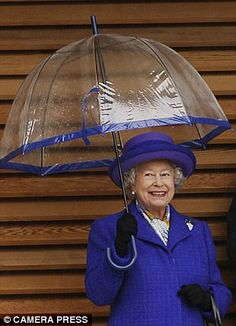 Queen Elizabeth II shelters from the rain at the official opening of the Lawn tennis associations National Tennis centre in Roehampton, UK. Cuando llueve, todos se mojan.