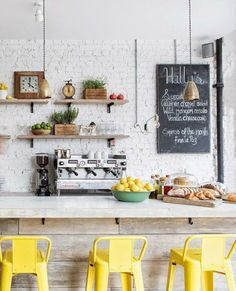Vintage-themed kitchen with a bright yellow bar stools, painted white brick, bright yellow barstools, pantone meadowlark, lemon yellow, bright yellow