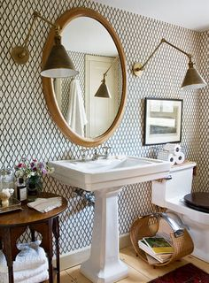 Super wow graphic bathroom with pedestal sink, black toilet seat, graphic wallpaper and super cool lighting.