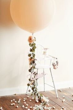 Elegant Balloon | This Haus of Ours wins for most epic first birthday high chair balloon ever! We love how the balloon ribbon was beautified with leaves and...