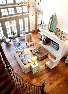 Love the contrast of the light airy furniture with the darker floor and I love the staircase and high ceilings!