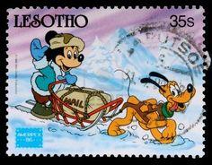 LESOTHO - alrededor de 1986: Una marca de 35-sente impresa en el Reino de Lesotho muestra el Disney caracteres del ratón Mickey y Pluto entregar correo por trineo de perros, alrededor de 1986