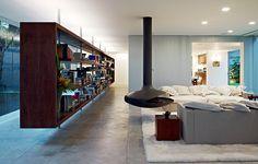 """O projeto do arquiteto Isay Weinfeld tem ambientes amplos e aberturas generosas para o exterior. """"Criei uma estante comprida que delimita áreas de entrada e social"""", diz. A peça tem desenho vazado para que se olhe através dela"""