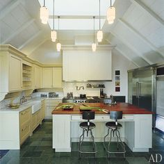 Soaring ceilings and dramatic skylights imbue this Long Island kitchen with an airy, barnlike feel.