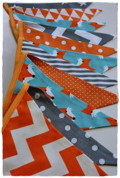 This adorable bunting is made with the cutest fabric! Teal, Orange and Grey - Foxes, Strips, Chevron and Dots make up this Fabric Bunting. ~Would add the perfect finishing touch to your baby's nursery, child's room or playroom.  ~ Makes an excellent baby shower gift. ~ A reusable eco-friendly decoration for birthday parties or baby showers.  ~ An adorable photography prop for your child's next photo shoot.  Each fabric bunting banner is made of double-sided flags in a mix colors. Flags…