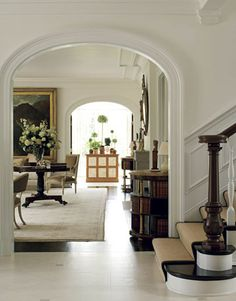 "From the foyer, views of the living room and conservatory unfold through arched doorways. ""I felt that this wide walkway needed strong symmetry and strong furniture,"" says William Hodgins. To that end, he placed a pair of large Sheraton consoles from Sentimento Antiques against one wall. Foyer floors are faux-painted marble tile."
