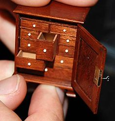 "The Adell Venus Collection of Miniatures | Maine Antique Digest This 1 5/8"" high Georgian-style mahogany specimen case by William R. Robertson features ten fitted and dovetailed drawers of differing sizes behind a paneled door that locks with an honest-to-God original key, and the bottom drawer holds a miniature business card. Estimated at $300/500, it sold for $9375."