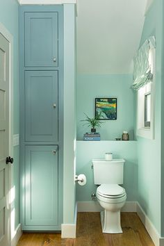 A partial wall in this downstairs bath creates a water closet on one side and a storage area on the other. A small shelf behind the toilet holds decorative items and bath accessories. Tip: If you're really tight on space, consider open shelves, which neatly stow towels and toiletries within easy reach without adding another door swing in the room.