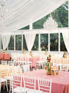 square dining tables at tented wedding   white chiavari chairs   pink and orange table cloths
