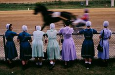 Accustomed to the pace of horse-drawn huggles and plows, Amish women watch a