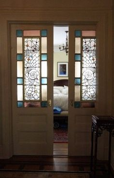 the stained glass pocket doors of the guest room on the second floor include original hardware