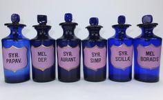 Six cobalt blue pink enamel labelled bottles with peg stoppers. Ground pontil marks to base. C1880